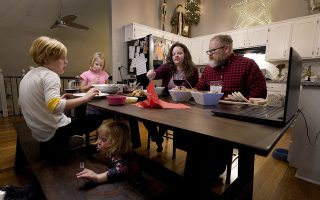 Jessica and John Franz have Thanksgiving dinner with their daughters, Amelia, 11, left; Molly, 8, back; and Quinn, 2, front, Thursday, Nov. 26, 2020, in Olathe, Kan. The family was having a quiet scaled-back Thanksgiving with just the household due to concerns about the coronavirus. (AP Photo/Charlie Riedel)