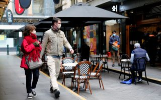 People walk past a cafe after the coronavirus disease (COVID-19) restrictions were eased for the state of Victoria, in Melbourne, Australia, October 28, 2020. REUTERS/Sandra Sanders
