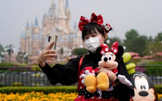 FILE PHOTO: A visitor dressed as a Disney character takes a selfie while wearing a protective face mask at Shanghai Disney Resort as the Shanghai Disneyland theme park reopens following a shutdown due to the coronavirus disease (COVID-19) outbreak, in Shanghai, China May 11, 2020. REUTERS/Aly Song/File Photo  GLOBAL BUSINESS WEEK AHEAD