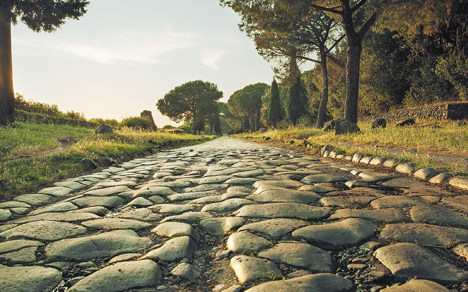 Η Αππία Οδός το δειλινό. Ηταν ο πιο μακρύς δημόσιος δρόμος που κατασκεύασαν οι Ρωμαίοι. Ξεκινούσε από τη Ρώμη, περνούσε από την Καμπανία και έφτανε στο Βρινδήσιον (σημερινό Μπρίντιζι). Οφείλει την ονομασία της στον τιμητή Κλαύδιο Αππιο, ο οποίος κατασκεύασε το πρώτο τμήμα το 312 π.Χ. (Φωτ. SHUTTERSTOCK)