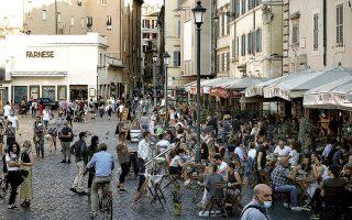 Ιταλοί απολαμβάνουν τον καφέ τους σε πλατεία της Ρώμης στα τέλη του περασμένου Μαΐου. Μετά την καραντίνα της άνοιξης και τη μείωση των κρουσμάτων παντού, στην κουρασμένη από τα μέτρα Ευρώπη υπήρξε χαλάρωση. (Cecilia Fabiano / La Presse via A.P.)