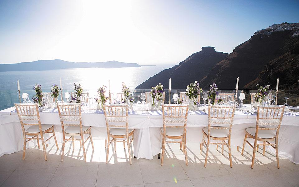 Γαμήλιο τραπέζι στη Σαντορίνη περιμένει τους νεονύμφους από το εξωτερικό. Οι γάμοι ξένων στην Ελλάδα, δραστηριότητα στην οποία εμπλέκονταν τα γραφεία που τους οργανώνουν, εταιρείες οπτικοακουστικών, φωτογράφοι, μακιγιέρ, κομμωτές, ανθοπώλες, ξενοδόχοι, εταιρείες ενοικίασης αυτοκινήτων κ.ά., έχουν «παγώσει» επ' αόριστον. (Φωτ. SHUTTERSTOCK)