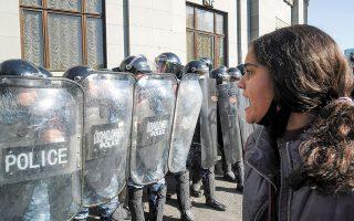 Aρμένια διαδηλώτρια κατά του πρωθυπουργού Νικόλ Πασινιάν, αντιμέτωπη με αστυνομικές δυνάμεις, χθες στο Ερεβάν (φωτ. REUTERS).