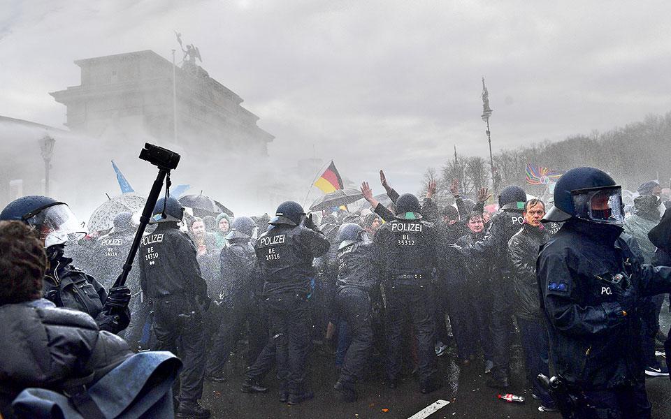 Με αντλίες νερού διέλυσε χθες η γερμανική αστυνομία τους διαδηλωτές στο Βερολίνο, οι οποίοι διαμαρτύρονταν για τα περιοριστικά μέτρα λόγω κορωνοϊού, συγκρίνοντάς τα με τους νόμους που διευκόλυναν τον Χίτλερ να ανέλθει στην εξουσία. Οι συγκεντρωμένοι αψήφησαν τις εκκλήσεις να φορέσουν μάσκες και να κρατήσουν αποστάσεις (φωτ. EPA / FILIP SINGER).