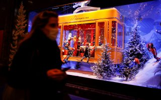 Pedestrians walk past a window display at the Printemps department store where lights are switched on for the Christmas season in Paris, France, November 17, 2020. REUTERS/Benoit Tessier