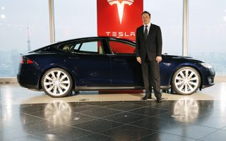 Tesla Motors Inc Chief Executive Elon Musk poses with a Tesla Model S electric car in Tokyo September 8, 2014. Musk said on Monday that he would not be surprised if there was a significant deal with Toyota Motor Corp in the next two to three years, though there were no definitive plans.  REUTERS/Toru Hanai (JAPAN - Tags: TRANSPORT BUSINESS) - RTR45C7R