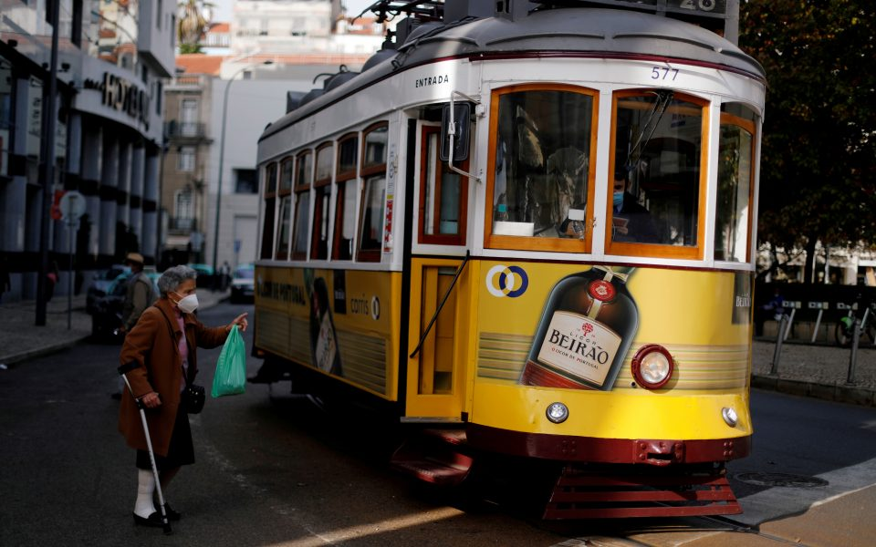 FILE PHOTO: A woman wearing a protective mask speaks with a driver of a tram during the coronavirus outbreak in Lisbon, Portugal, October 31, 2020.  REUTERS/Rafael Marchante/File Photo