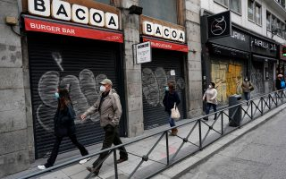 People walk near closed shops amid the coronavirus disease (COVID-19) outbreak in Madrid, Spain, November 4, 2020. REUTERS/Juan Medina