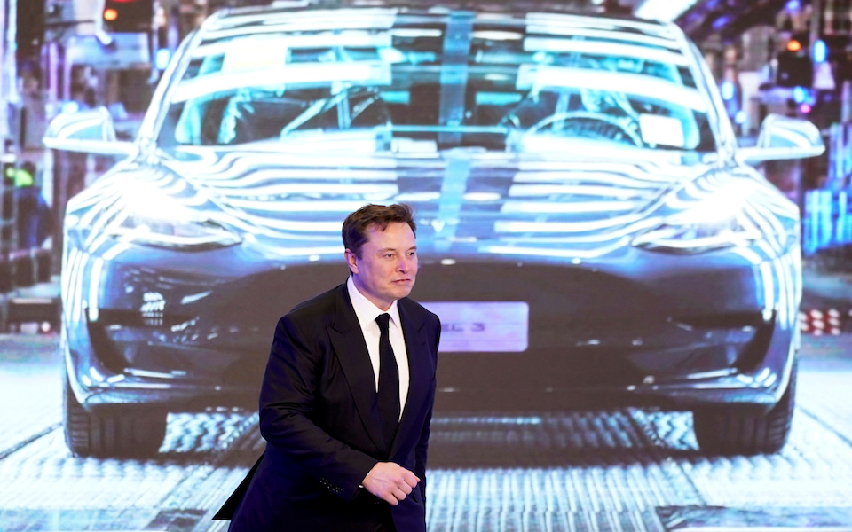 FILE PHOTO: Tesla Inc CEO Elon Musk walks next to a screen showing an image of Tesla Model 3 car during an opening ceremony for Tesla China-made Model Y program in Shanghai, China, January 7, 2020. REUTERS/Aly Song/File Photo