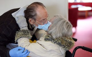 Bob Underhill, 84, and his wife Patricia, 82, suffering from Alzheimer's, kiss through a face mask as they are allowed to visit with physical contact for the first time at The Chiswick Nursing Centre, which has introduced a coronavirus disease (COVID-19) test with results ready in thirty minutes, in London, Britain December 2, 2020.  REUTERS/Kevin Coombs