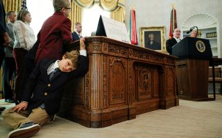 Sammy Olszta, 6, grandson of U.S. Olympic wrestling Gold Medalist and Presidential Medal of Freedom recipient Dan Gable, leans against the Resolute Desk as Gable delivers remarks beside U.S. President Donald Trump during a presentation ceremony inside the Oval Office at the White House in Washington, U.S., December 7, 2020. REUTERS/Tom Brenner