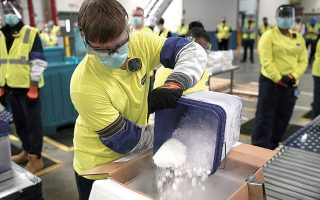Εργαζόμενος της Pfizer στο Μίσιγκαν των ΗΠΑ τοποθετεί ξηρό πάγο σε συσκευασία που περιέχει εμβόλια των Pfizer/BioNTech, η παραγωγή των οποίων έχει ξεκινήσει. (Φωτ.  EPA / MORRY GASH)