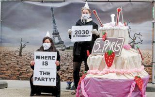Ακτιβιστές έξω από το κτίριο όπου διεξαγόταν η Σύνοδος Κορυφής της Ε.Ε. στις 10 Δεκεμβρίου, με φόντο τον Πύργο του Αϊφελ γερμένο σε έναν μελλοντικό ερημοποιημένο κόσμο και με μια τούρτα, η οποία αντί για κεράκια είχε θερμόμετρα, θύμιζαν στους ηγέτες ότι πέντε χρόνια μετά το Παρίσι έχουν γίνει πολύ λίγα για το περιβάλλον. (Φωτ. EPA / STEPHANIE LECOCQ)