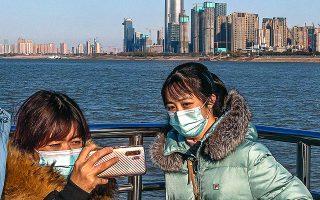 Στη Γουχάν η ομαλότητα μπορεί να επανέρχεται, όμως η χρήση μάσκας παραμένει υποχρεωτική. Φωτ. EPA