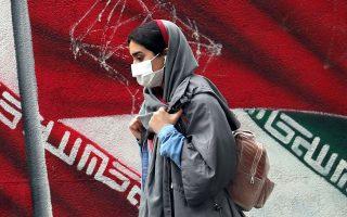 Nεαρή Ιρανή με φόντο τη σημαία της χώρας, σε δρόμο της Τεχεράνης (φωτ. EPA).