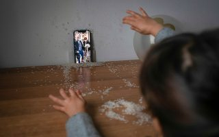 Bianca Toniolo, 3, throws confetti as she watches her grandfather Massimo's wedding ceremony live on video call from the island of Sardinia, which her family were unable to attend in person due to strict coronavirus disease (COVID-19) regulations banning travel between regions, at their home in San Fiorano, Italy, January 5, 2021. The only people attending the wedding ceremony were Massimo Toniolo, his newlywed wife Graziella Pinna and the family of her son from the Sardinian town of Maracalagonis. REUTERS/Marzio Toniolo