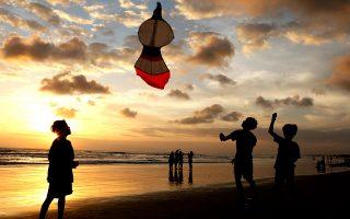 Παιδιά πετούν χαρταετό στην παραλία Kuta, στο Μπαλί. © AP Photo/Firdia Lisnawati