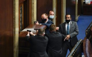 Τα πρώτα λεπτά του τρόμου. Ανδρες της ασφάλειας του Καπιτωλίου προσπαθούν, με προτεταμένα τα όπλα, να κρατήσουν εκτός της αίθουσας τους αγριεμένους διαδηλωτές, προκειμένου να προλάβουν να φυγαδευτούν οι βουλευτές και οι γερουσιαστές. Φωτ. AP Photo/Andrew Harnik