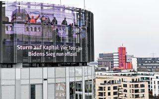 Γιγαντοοθόνη σε κτίριο στο Εσεν της Γερμανίας δείχνει την επίθεση στο Καπιτώλιο στην Ουάσιγκτον. Προ ολίγων εβδομάδων, διαδηλωτές είχαν περικυκλώσει και τη γερμανική Βουλή, αλλά απωθήθηκαν από τις δυνάμεις ασφαλείας. (Φωτ. A.P./Martin Meissner)