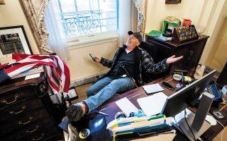 «Ο άνδρας που φωτογραφήθηκε να ξεκουράζει τα πόδια του στο γραφείο της Πελόσι έμοιαζε να νιώθει σαν βασιλιάς για μία μέρα», σημειώνει ο Thomas Meaney. (Φωτ. EPA/JIM LO SCALZO)