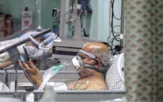 Το τηλέφωνο αποτελεί παρηγοριά για τους νοσηλευόμενους με κορωνοϊό, αφού δεν επιτρέπεται να δέχονται επισκέψεις. Παίρνουν δύναμη αλλά και δίνουν κουράγιο στους οικείους τους. Στη φωτογραφία ασθενής σε νοσοκομείο της Γάζας. (Φωτ. EPA/MOHAMMED SABER)