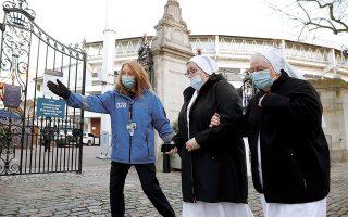 Δύο καλόγριες λίγο πριν εμβολιαστούν, στο Λονδίνο. Η μετάλλαξη που εντοπίστηκε στη Βρετανία έχει αυξημένη ικανότητα μετάδοσης κατά 60% έως 70% (REUTERS / John Sibley).