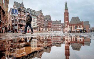 Eνας άνδρας με μάσκα περπατάει σε κεντρική πλατεία της Φρανκφούρτης στη Γερμανία. Με τη διαδικασία του εμβολιασμού να καθυστερεί στη χώρα, η κυβέρνηση εξετάζει το ενδεχόμενο λήψης πρόσθετων μέτρων. Σε αυτά περιλαμβάνεται η επιβολή περιορισμών στην είσοδο επισκεπτών από Βρετανία, Πορτογαλία, Βραζιλία και Νότια Αφρική, όπου τα μεταλλαγμένα στελέχη έχουν μεγάλη διασπορά.  (φωτ. A.P. Photo / Michael Probst).