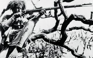 In this British Official Photo, an Abyssinian marksman takes to a tree for a vantage point during a successful assault by native troops on the Italian held fort of Debra Marcos in Ethiopia on May 22, 1941. (AP Photo/British Official Photo)