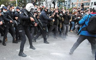 Aστυνομικός ρίχνει πλαστικές σφαίρες στο έδαφος για να διαλύσει διαμαρτυρόμενους φοιτητές στην Κωνσταντινούπολη. (Φωτ. EPA / TOLGA BOZOGLU)