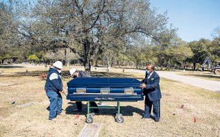 Eργολάβος κηδειών και υπάλληλοί του μεταφέρουν προς ταφή το φέρετρο με τη σορό ακόμη ενός Αμερικανού πολίτη που νικήθηκε από επιπλοκές εξαιτίας της COVID-19, στο Χιούστον του Τέξας (φωτ. REUTERS).