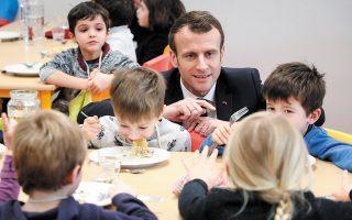 Γάλλος μαθητής δημοτικού παίρνει το σχολικό γεύμα του παρέα με τον πρόεδρο Εμανουέλ Μακρόν. (Φωτ. A.P.)