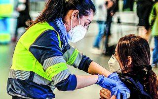 Aστυνομική υπάλληλος λαμβάνει το εμβόλιο της AstraZeneca κατά τη διάρκεια μαζικού εμβολιασμού στο στάδιο Wanda Metrpolitano της Μαδρίτης. Φωτ. A.P.