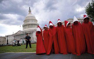Γυναίκες ντυμένες «θεραπαινίδες» από το «Handmaid's Tale» έξω από το Καπιτώλιο διαμαρτύρονται για το νομοσχέδιο της Υγείας. ©Eric Thayer/The New York Times
