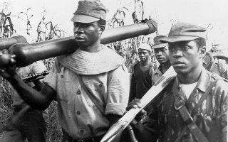 Απρίλιος 1974. Ανδρες του FRELIMO μεταφέρουν τμήματα πυροβόλου και οβίδες στην πορτογαλική αποικία της Μοζαμβίκης.  Φωτ. ASSOCIATED PRESS