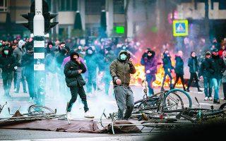 Η παραδοσιακά ήσυχη Ολλανδία ζει άγριες νύχτες, με επαναλαμβανόμενες συγκρούσεις (φωτ. από το Αϊντχόφεν) μεταξύ νέων διαδηλωτών και αστυνομίας, από τις 23 Ιανουαρίου, όταν ανακοινώθηκαν αυστηρά περιοριστικά μέτρα. Φωτ. EPA