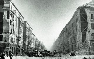 Κατεστραμμένα κτίρια και σοβιετικά οχήματα, ανάμεσά τους και ένα άρμα μάχης, σε κεντρικό δρόμο της Βουδαπέστης κατά την ουγγρική επανάσταση του 1956 εναντίον του κομμουνιστικού καθεστώτος της χώρας, την οποία η Μόσχα έπνιξε στο αίμα. Φωτ. SHUTTERSTOCK