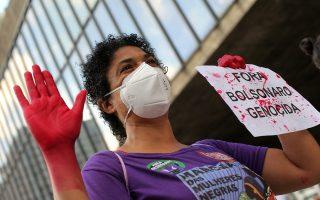 Μια διαδηλώτρια στο Σάο Πάουλο κρατά με «ματωμένα χέρια» πλακάτ διαμαρτυρίας κατά του προέδρου της Βραζιλίας που γράφει «'Εξω Μπολσονάρου, Γενοκτονία» (Φωτ.: REUTERS/Carla Carniel).