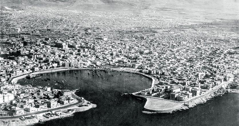 Το Πασαλιμάνι, η συνοικία Τσίλλερ και η Καστέλλα με το μέτωπο των νεοκλασικών μεγάρων με θέα τη θάλασσα, το 1939. Πιο πίσω, οι γειτονιές των Κρητικών μεταναστών και στο βάθος ο μεγάλος προσφυγικός οικισμός της Νέας Κοκκινιάς. Φωτ. Αρχείο ΥΠΕΧΩΔΕ, ψηφιακή συλλογή Γιώργου Βεράνη