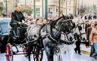 Στιγμιότυπο από την κηδεία του Γρηγόρη Μπιθικώτση με το μαύρο και το άσπρο άλογο, και τον πατέρα του, Ευθύμιο, στην άμαξα.