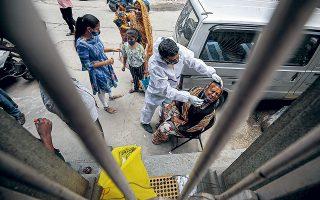 Υγειονομικός υπάλληλος διεξάγει τεστ για COVID-19 στη Μπαγκαλόρ της Ινδίας. Μέσα σε μια ημέρα εντοπίστηκαν στην ασιατική χώρα 217.353 κρούσματα κορωνοϊού, αριθμός που συνιστά νέο αρνητικό ρεκόρ (φωτ. EPA).