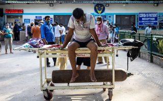 Yγειονομικός υπάλληλος μεταφέρει μια φιάλη οξυγόνου σε νοσοκομείο στο Νέο Δελχί (φωτ. REUTERS/Danish Siddiqui).