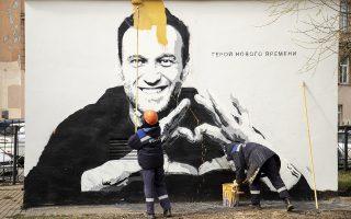 Υπάλληλος του Δήμου της Αγίας Πετρούπολης προσπαθεί να σβήσει γκράφιτι που δείχνει τον Αλεξέι Ναβάλνι και γράφει τις λέξεις «Ήρωας της Εποχής μας» (φωτ.: AP PΗΟΤΟ/Ivan Petrov).