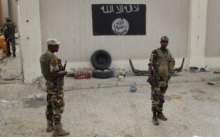 Φωτ. αρχείου AP/Jerome Delay - Νιγηριανοί στρατιώτες μπροστά σε σημαία της Μπόκο Χαράμ, μετά την ανακατάληψη της πόλης Damasak