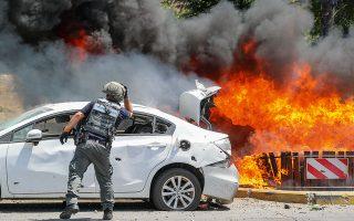 Πυροτεχνουργός του ισραηλινού στρατού μπροστά από τη φωτιά που κατακαίει οχήματα, μετά τον καταιγισμό ρουκετών της Χαμάς από τη Λωρίδα της Γάζας στη νότια πόλη Ασκελον του Ισραήλ (φωτ. A.P. Photo/Ariel Schalit).