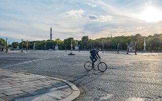 Ενας άνδρας διασχίζει την Πλας ντε λα Κονκόρντ στο Παρίσι με το ποδήλατο. Η δήμαρχος της γαλλικής πρωτεύουσας, Αν Ινταλγκό, φιλοδοξεί να πεζοδρομήσει, εκτός από την εικονιζόμενη πλατεία, αυτήν της Βαστίλλης και το σύνολο της λεωφόρου Σεν Ζερμέν (φωτ. A.P. Photo/Thibault Camus).