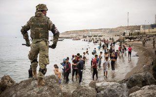 Μετανάστες που μόλις έχουν φθάσει στον ισπανικό θύλακο Θέουτα από το έδαφος του Μαρόκου βρίσκονται αντιμέτωποι με τον ισπανικό στρατό. Μέσα σε ένα 24ωρο έξι χιλιάδες άνθρωποι πέρασαν σε ισπανικό έδαφος, σε μια άσκηση πιέσεων του Μαρόκου προς τη χώρα της Ιβηρικής (φωτ. A.P. Photo / Javier Fergo).