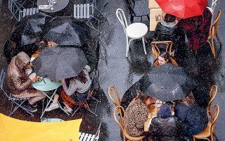 Παρά τη δυνατή βροχή, οι Παριζιάνοι δεν έχασαν την ευκαιρία να απολαύσουν το φαγητό τους στα εστιατόρια την πρώτη μέρα χαλάρωσης των περιορισμών (φωτ. EPA/YOAN VALAT).