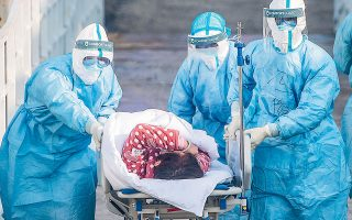 Aρχές Φεβρουαρίου 2020. Κινέζοι υγειονομικοί μεταφέρουν ασθενείς σε ένα ολοκαίνουργο νοσοκομείο, στη Γουχάν. Σύμφωνα με κυβερνητικές πηγές, οι μολύνσεις από COVID-19 είχαν μόλις ξεπεράσει τις 20.000 (φωτ. A.P.).