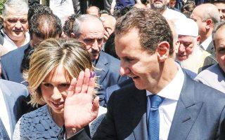 O Μπασάρ Αλ Ασαντ και η σύζυγός του Ασμα αποχωρούν από το εκλογικό κέντρο όπου ψήφισαν, στην Ντούμα (φωτ. EPA).