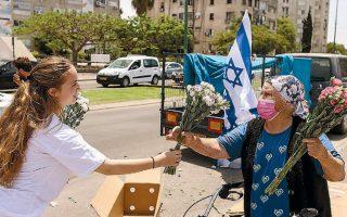 Προσφορά λουλουδιών μετά την εκεχειρία, σε εμπορικό κέντρο της ισραηλινής πόλης Ασκελόν (φωτ. REUTERS/Ronen Zvulun).